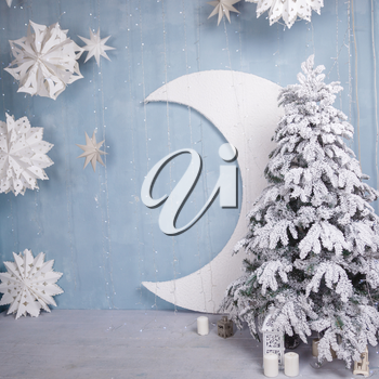 A beautiful snow-covered tree with a month and garlands. New Year and Christmas decorations. White and blue