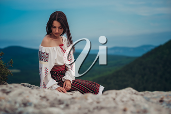 Atractive woman in traditional romanian costume on mountain green blurred background. Outdoor photo. Traditions and cultural diversity
