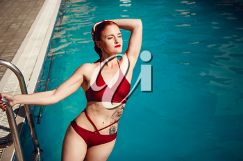 Enjoying suntan and vacation. Colorful portrait of pretty young woman in red swimsuit lying near swimming pool.