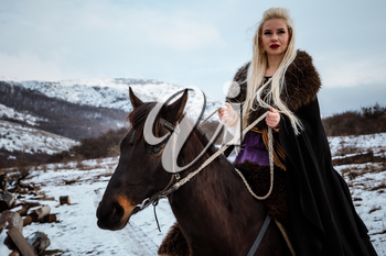 Beautiful young blonde on a crow. Woman viking with a black horse against the background of mountains