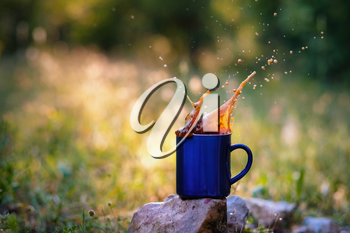 Blue mug of hot tea or coffee with milk, outdoor, the concept of travel, spray, splash. Glare on the pictures from the setting sun, pleasant bokeh