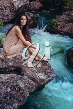 Young woman in the dress is sitting on the stone in the middle of a creek. Fashionable toning.