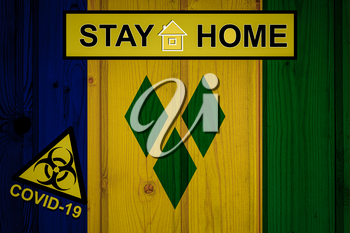 Flag of the Saint Vincent and the Grenadines in original proportions. Quarantine and isolation - Stay at home. flag with biohazard symbol and inscription COVID-19.