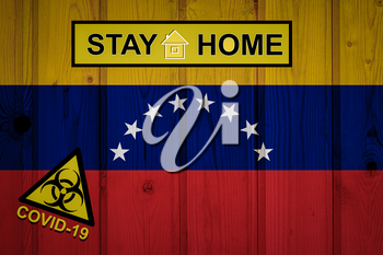 Flag of the Venezuela in original proportions. Quarantine and isolation - Stay at home. flag with biohazard symbol and inscription COVID-19.