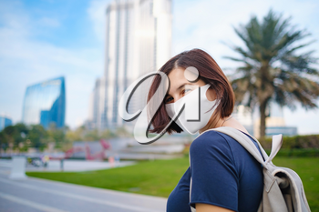Portrait of beautiful woman wearing a mask for prevent virus walking in Dubai with skyscrapers in the background. Enjoying travel in United Arabian Emirates.
