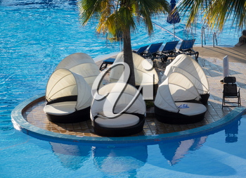 Circular relaxing beds and loungers with shades by side of hotel swimming pool