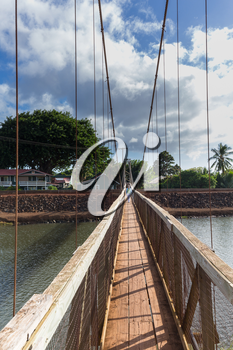 Wide angle view across the famous wooden suspension swinging bridge to cross the river in Hanapepe Kauai