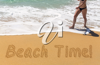 Beach Time words written into sand on beach by warm ocean as young woman walks along the shoreline advertizing vacations and holidays