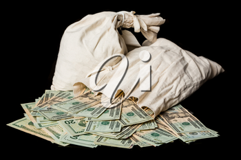 Thousands of US dollars pouring out of a cloth money bag onto a black background showing many currency notes or bills. Second money bag in the background