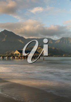Swimmer stands in the ocean as the rising sun illuminates the peaks of Na Pali mountains over the calm bay and Hanalei Pier