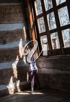 Small and lonely caucasian baby girl or toddler standing inside empty old wooden cabin to suggest poverty or recession