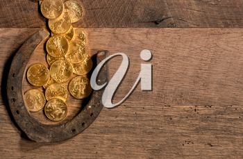 Treasure of pure gold coins flowing on rustic wooden table into horseshoe to celebrate luck on St Patrick's Day