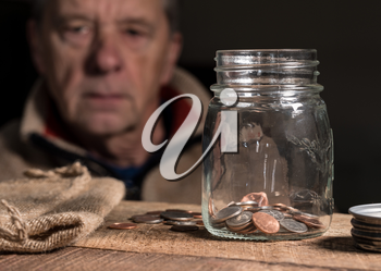 Senior man or retiree looking at glass savings jar in depression as he sees how little money is left