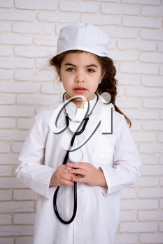 Little girl doctor in the white uniform with stethoscope