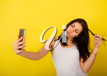 Young cute girl in casual clothes dabbles and grimaces and takes a selfie on her smartphone against a bright yellow background