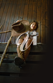 Little girl in a wide-brimmed cowboy hat and traditional dress in high boots and with a lasso posing on a dark wooden background