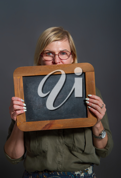 Adult woman holding a blank chalk board on a dark background