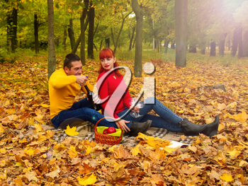 husband and wife in bright clothes for relaxing settled down on a picnic among the trees and fallen leaves with a bottle of wine and glasses.