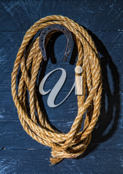 a steel horseshoe and a rough lasso rope hang on a dark wooden wall