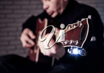 adult man playing classic wooden acoustic guitar close up