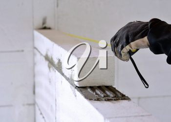 The bricklayer measures a newly built wall with a tape measure.