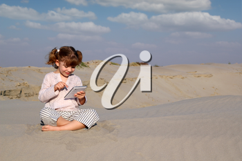 happy little girl play with tablet pc in desert