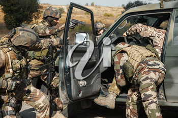 Squad of elite french paratroopers of 1st Marine Infantry Parachute Regiment RPIMA detaining terrorist in the car