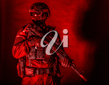 Police assault team member, special forces soldier, private security service, military company serviceman in black ammunition and uniform, armed service rifle, high contrast studio shoot on black