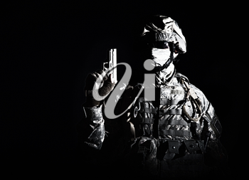 Elite troops fighter, US special operations forces soldier, marine in combat uniform and ammunition with hidden behind mask and glasses face standing in darkness with raised up service pistol in hand
