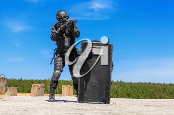 Swat police special forces operators storming criminals terrorists hiding behind ballistic shield. Blue sky daylight