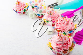 Decorated pink birthday cupcakes  and cookware. Birthday homemade cupcakes decorating process.  Sweet dessert  pastry with whipped cream.