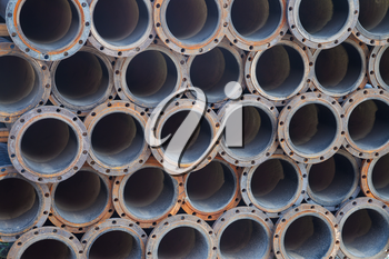 Stacked steel pipe bundle in industrial stockyard texture background