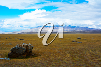 Mountain View steppe landscape, a piece of rock in the foreground, blue sky with clouds. Chuya Steppe,  Kuray steppe in the Siberian Altai Mountains, Russia