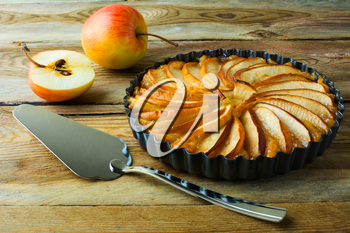 Traditional apple pie, fruit dessert, tart with fresh apples on wooden rustic table, selective focus