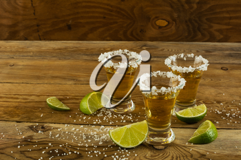Three shots of gold tequila with lime and salt on the wooden background. Tequila shot. Gold Mexican tequila. Tequila