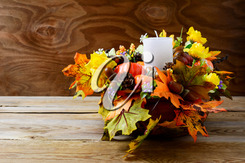 Thanksgiving decoration with white candle and silk fall leaves . Thanksgiving background with fall decor. Fall background. Copy space.