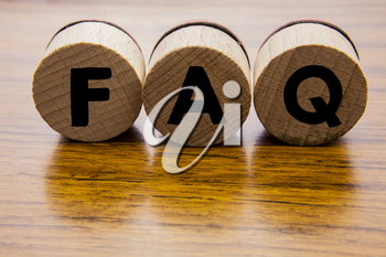Frequently Asked Questions on the wooden round wheels. Concept of the FAQ word on the wooden background. Web design concept. Caligraphy on the wooden objects.
