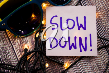 Slow Down handwritten on light pink note paper with blue color. Two sunglasses in different colors with wooden background and some lights are spread. Warning and suggestion Business concept.