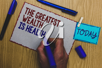 Conceptual hand writing showing The Greatest Wealth Is Health. Business photo text being in good health is the prize Take care Man holding marker paper clothespin express ideas wooden table