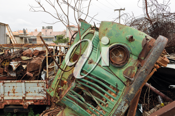 Rusty vintage car and scrap metal at a junkyard.