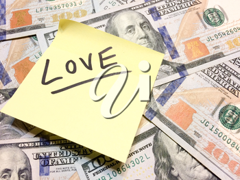American cash money and yellow post it note with text Love in black color aerial view