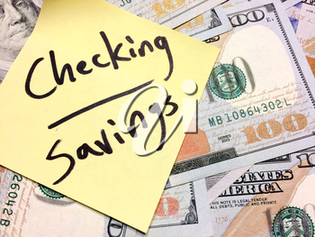 American cash money and yellow sticky note with text Checking and savings in black color aerial view