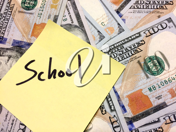 American cash money and yellow sticky note with text School in black color aerial view