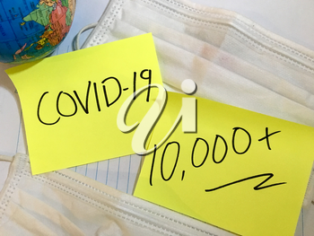 Coronavirus COVID-19 infection medical cases and deaths numbers. China COVID respiratory disease influenza virus statistics hand written on surgical mask and earth globe background