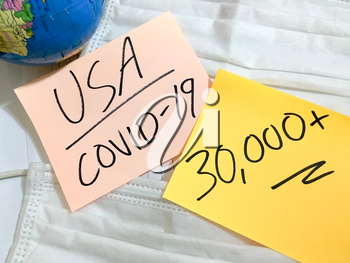 USA Coronavirus COVID-19 infection medical cases and deaths United States. China COVID respiratory disease influenza virus statistics hand written on surgical mask and earth globe background