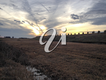 Sunset over farm field countryside on winter day with stream