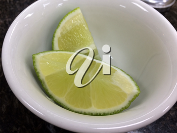 bright green fresh Lime slice in white bowl close up