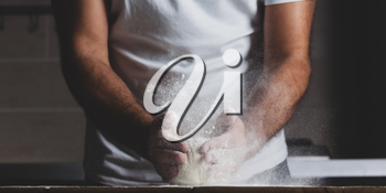 Man kneads raw dough, dust from flour flies in different directions, male hands on a black background