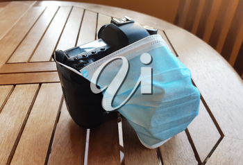 Surgical protective mask on reflex camera. Metaphor about the negative effect of the pandemic, caused by the coronavirus covid-19, on the photographic sector.