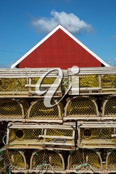 Yellow lobster cage in front of a red barn in Prince edward island, Canada